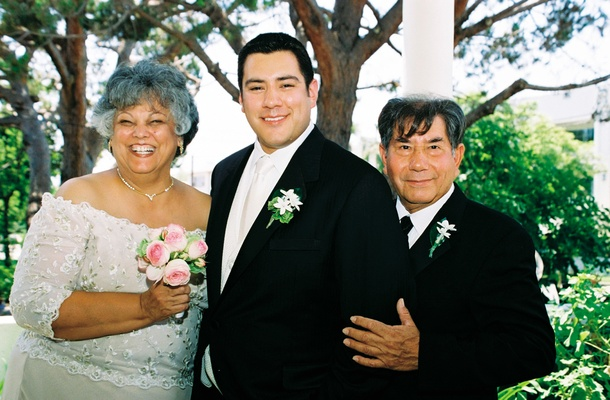 Groom with mother of groom and father at outdoor wedding