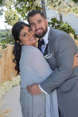 groom in grey suit and black bow tie with mother of groom in beaded dress with shawl wrap