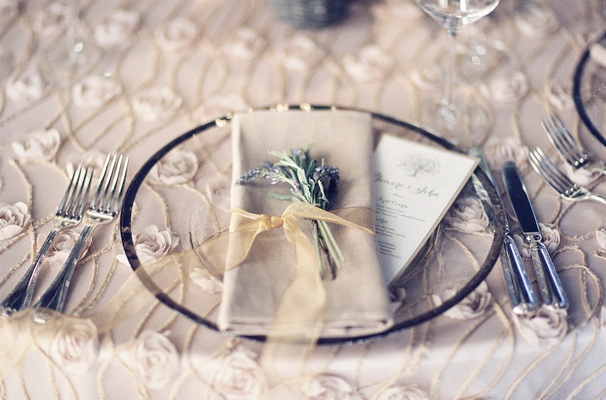 Wedding reception table linen with rimmed charger plate, rosette texture tablecloth, ribbon napkin