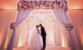 bride and groom kiss and hold hands under ceremony altar