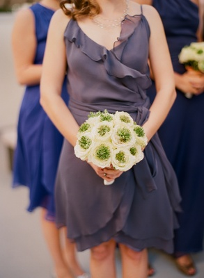 Bridesmaids in different dresses holding flowers