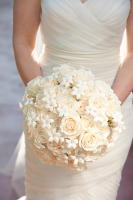 Bride holding round white bouquet with roses and pearls