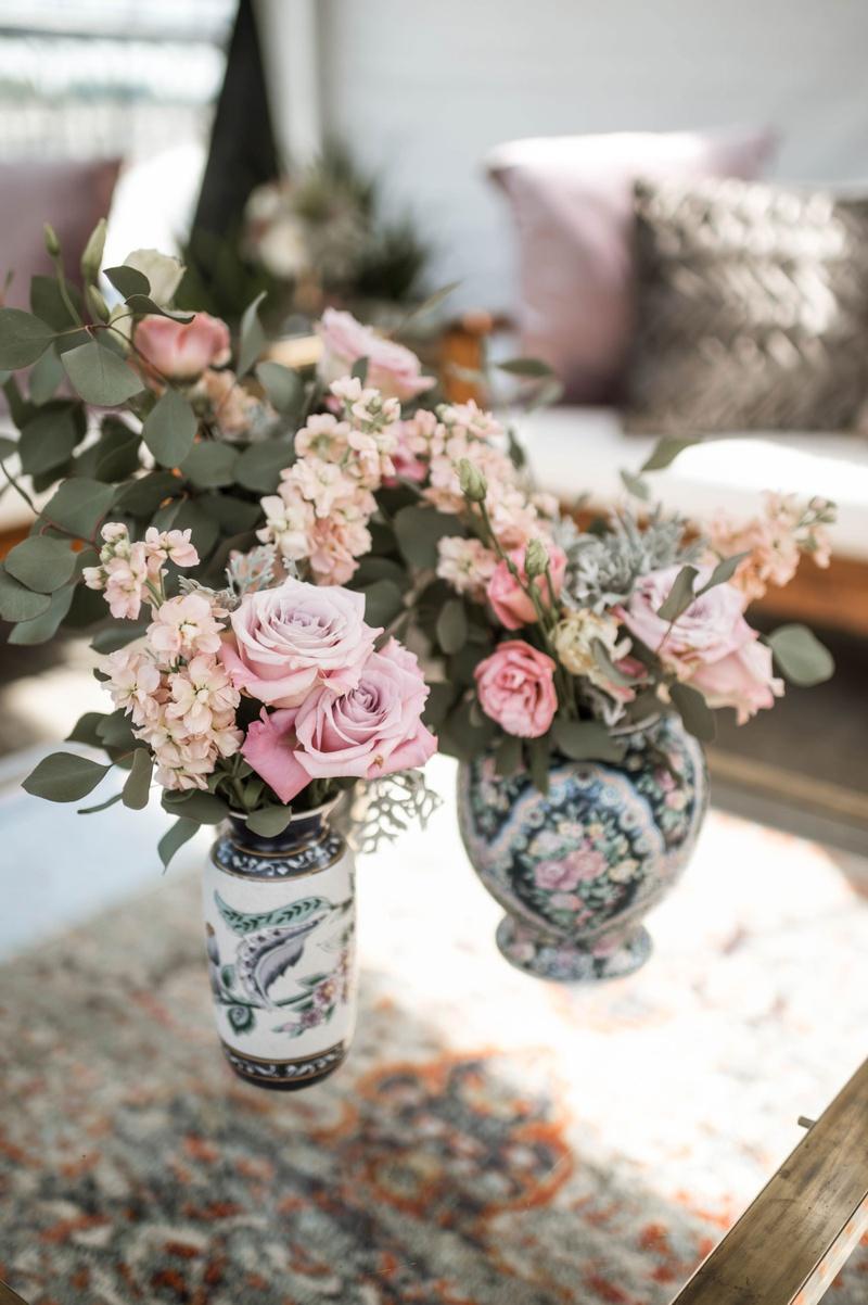 wedding reception lounge area vintage area rug painted vase pink flowers greenery