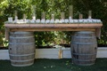 wedding escort cards displayed on table of wine barrels, candles in glass hurricanes