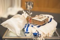 Holy book, white tallit with blue stripes, Michael Aram kiddush cup, satin bag at Jewish wedding