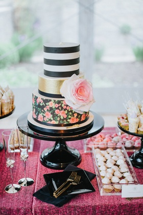 three tiered cake with floral wall paper tier, gold tier, black-and-white striped tier