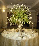 Wedding reception place card table with a centerpiece of white tulips and candles