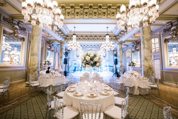 reception centerpiece with white peonies and hydrangeas with soft greenery on tall crystal stansd