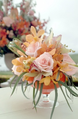 Wedding ceremony arrangement of pink and orange flowers with greenery in a cocktail glass