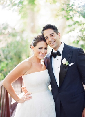 Bride in strapless Vera Wang gown with updo and groom in midnight blue tuxedo