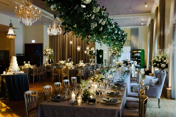 wedding reception greenery over long tables wedding cake chandelier hedge candles