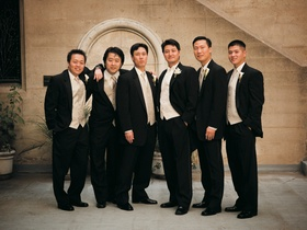 Groom and groomsmen in black tuxedos with cream vests and ties