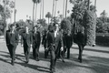 Black and white photo of groom and groomsmen walking on the lawn of The Beverly Hills Hotel