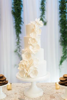 four tier white wedding cake with white sugar flowers