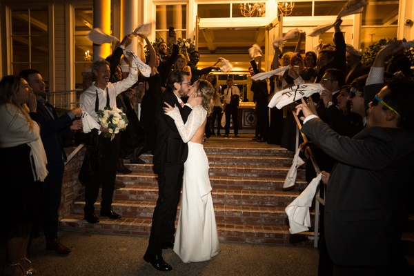 bride and groom kiss at grand exit while guests wave rally rags, baseball details at wedding