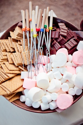Bowl of skewers, crackers, chocolate, and marshmellows