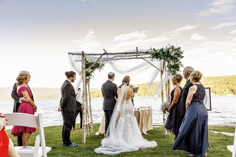 jewish wedding with chuppah made of birch and drapery, ceremony on shore of lake