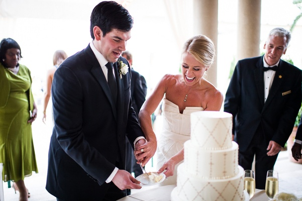 Bride and groom cut cake together at reception