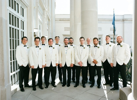 Groom and groomsmen with white tuxedo jackets black pants and bow ties lily of the valley
