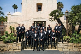 large group of groomsmen in tuxedos posed in front of old mission church