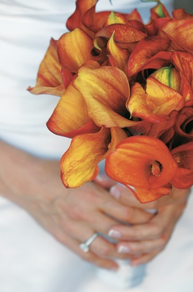 Bride holds bouquet of orange calla lily flowers
