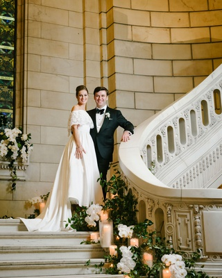 bride in mother's wedding dress groom in tuxedo on staircase greenery pillar candles white flowers