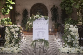 wedding ceremony sign with greenery on top and bottom
