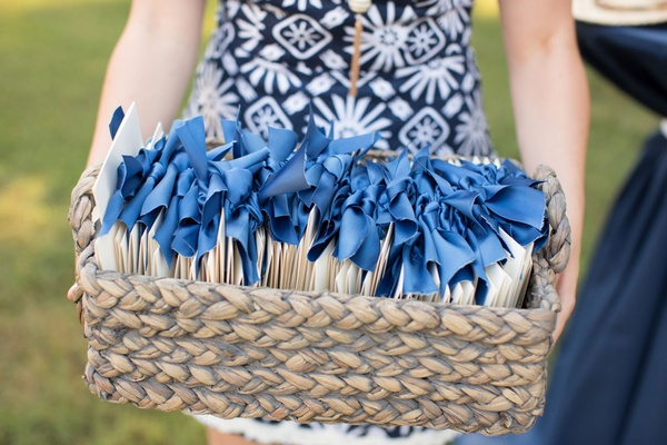 Wedding ceremony programs in tan basket with blue ribbon guest holding bin