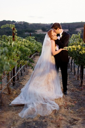 Bride and groom kissing in wedding attire at vineyard