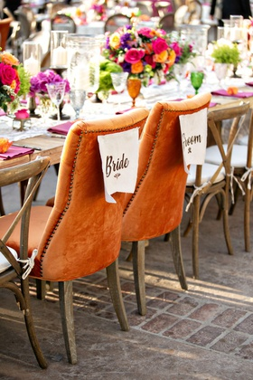wedding reception colorful boho chic outdoor orange nailhead velvet chairs head table wood seating
