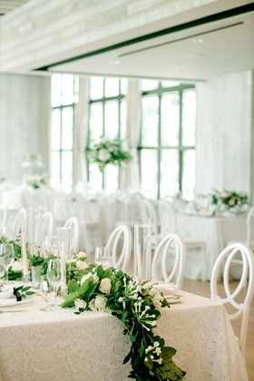 wedding reception long table white linen greenery white rose flower centerpiece runner taper candles