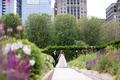 bride in monique lhuillier wedding dress ostrich feather skirt with groom in tuxedo greenery skyline
