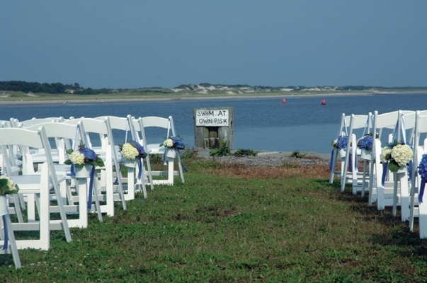 White ceremony chairs on grass lawn in front of bay