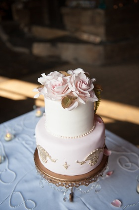 Wedding cake with pink layer and white layer with gold details and flowers