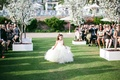 Flower girl walking down grass aisle with wand