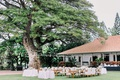wedding reception venue outdoor plantation lawn string lights wood tables and chairs