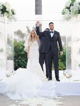 Bride in wedding dress with groom Levine Toilolo Atlanta Falcons football player hands in air