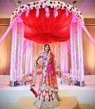 Indian bride in red and pink sari in front of red altar