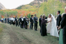 Newlyweds thanking guests outside with fall leaves