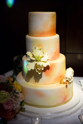 Four layer ombre wedding cake orange and yellow with sugar flower and dog replica on side wedding