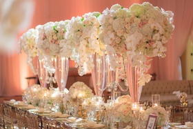 Tall wedding reception centerpieces with orchids, hydrangeas, roses on table with clear chairs