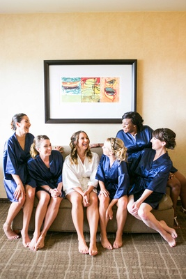 bride in white robe, bridesmaids in navy robes laughing