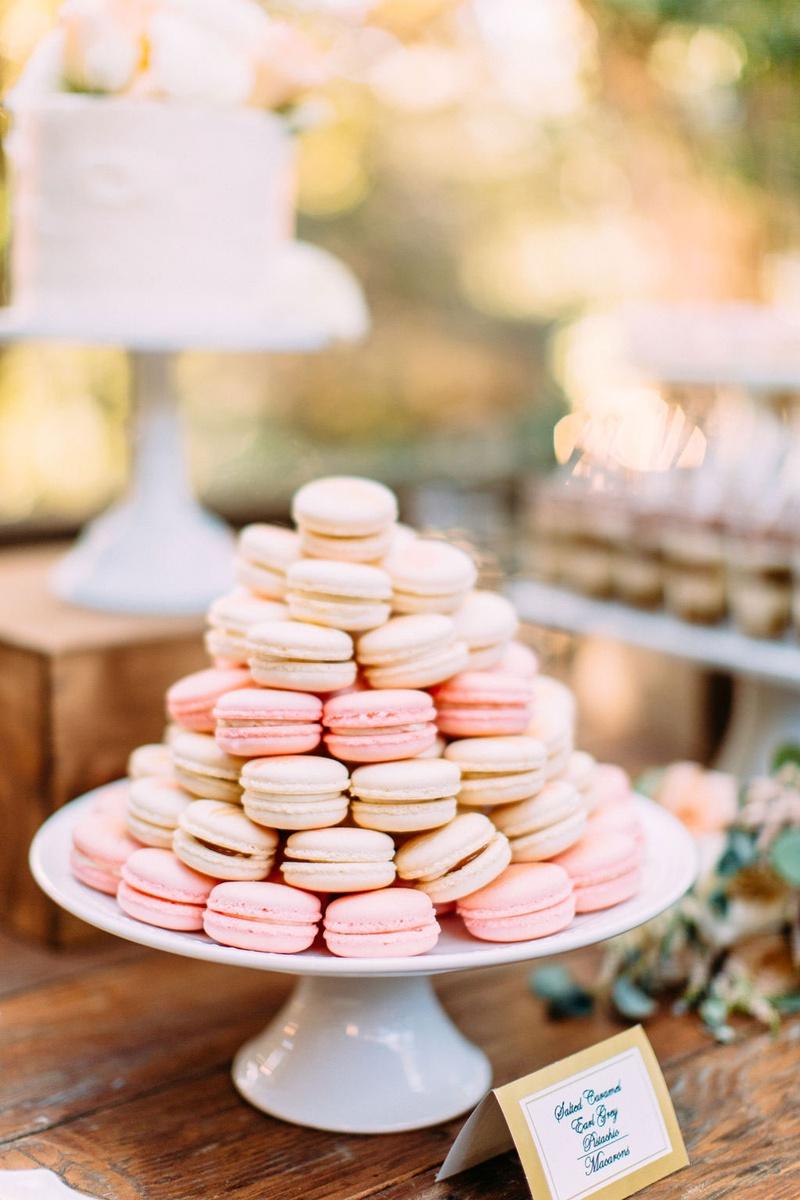 wedding reception dessert table white cake stand with pink white macaron desserts