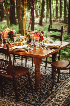Outdoor wedding reception with wood table, gold candelabra, and gold rimmed stemware