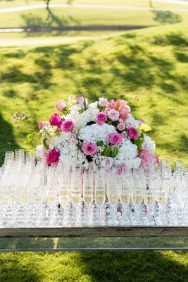 Wedding ceremony outdoor wedding pink rose white hydrangea champagne poured into flutes glasses