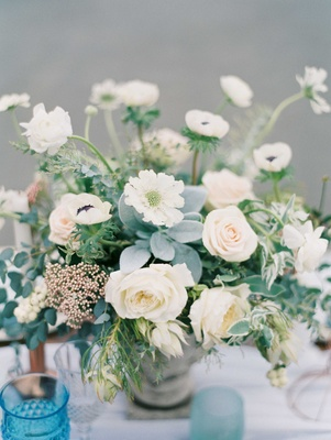 low floral arrangement of white and blush flowers with green foliage on blue white tablescape