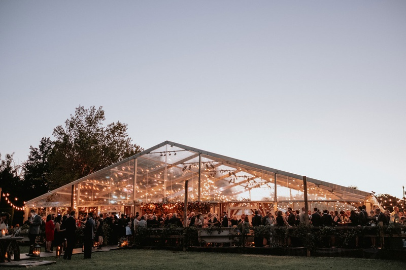 wedding reception tent on private estate lawn string lights greenery guests