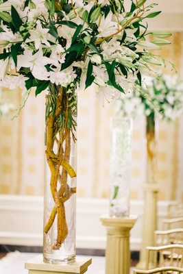 Wedding ceremony with bouquet of ivory stargazer lilies and orchids in a cylider vase decorate aisle