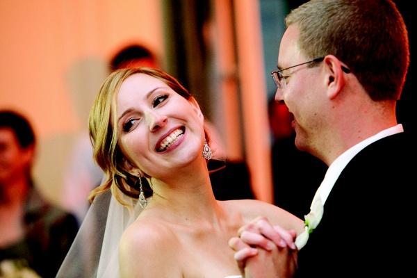 Bride in silver earrings dancing with groom