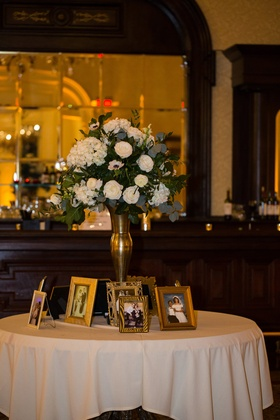 wedding table with family wedding portraits, floral arrangement in gold stand with ivory flowers